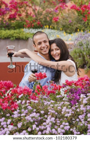 Hispanic couple hugging with wine