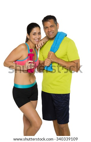 Hispanic couple in workout attire. Female is holding water bottle and male has towel on shoulder. Both are looking at camera and smiling. Isolated on white background.  - stock photo