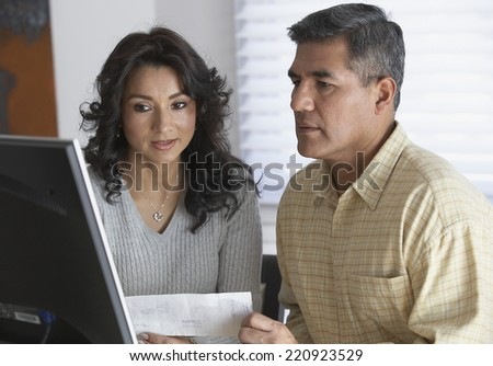 Hispanic couple looking at computer - stock photo