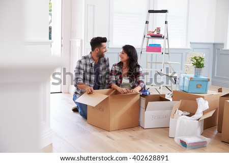 Hispanic Couple Moving Into New Home And Unpacking Boxes - stock photo