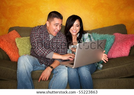 Hispanic Couple on Green Couch with Computer - stock photo