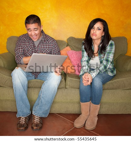 Hispanic Couple on Green Couch with Computer Woman is Bored - stock photo