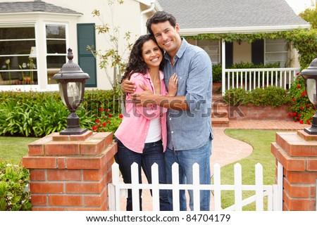 Hispanic couple outside home - stock photo