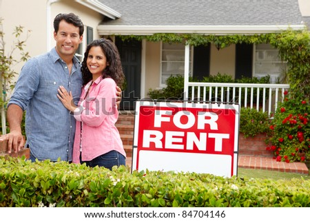 Hispanic couple outside home for rent - stock photo