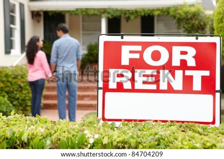 Hispanic couple outside home for rent - stock photo