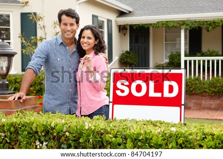 Hispanic couple outside home with sold sign - stock photo