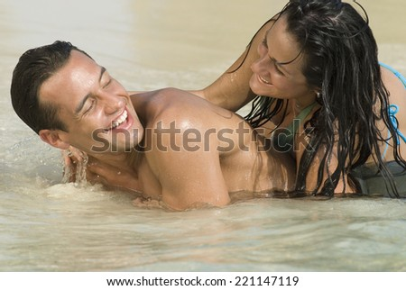 Hispanic couple playing in water - stock photo