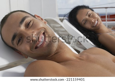 Hispanic couple sunbathing