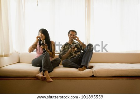 Hispanic couple talking on cell phones