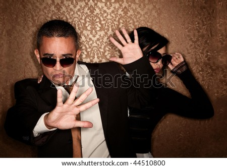 Hispanic couple trying not to be photographed - stock photo