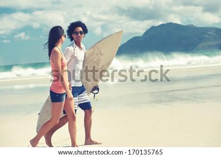 Hispanic couple walk on beach together with surfboard having fun outdoors - stock photo