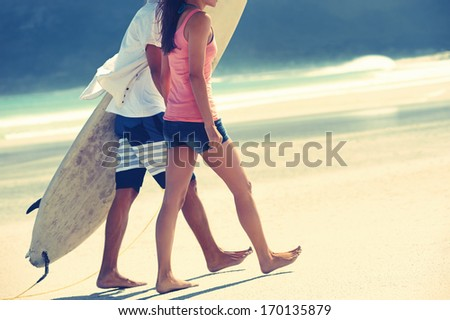 Hispanic couple walk on beach together with surfboard having fun outdoors - stock photo