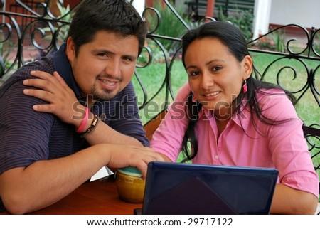 Hispanic couple with a laptop - stock photo