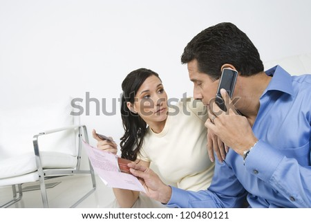 Hispanic couple with credit card and bill using cell phone