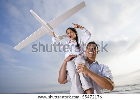 Hispanic dad and 9 year old child playing at beach with model plane - stock photo