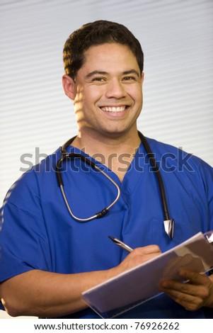 Hispanic Doctor Wearing Scrubs with Stethoscope around Neck - stock photo