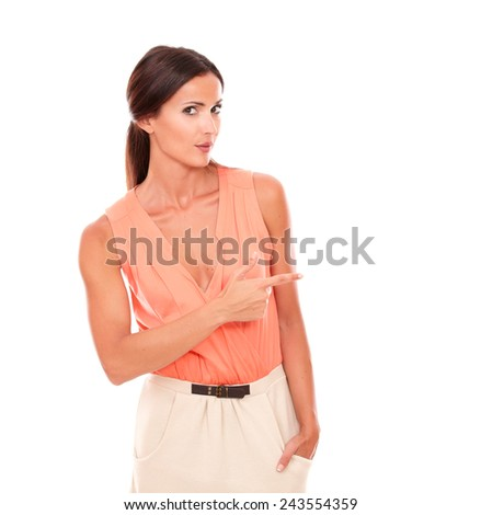 Hispanic elegant lady with fingers gesturing pointing to her left while looking at you in white background - copyspace - stock photo