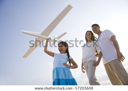 Hispanic family and 9 year old daughter having fun with toy plane - stock photo