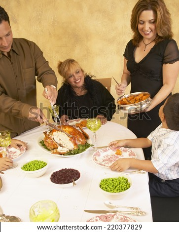 Hispanic Family At Holiday Dinner Table