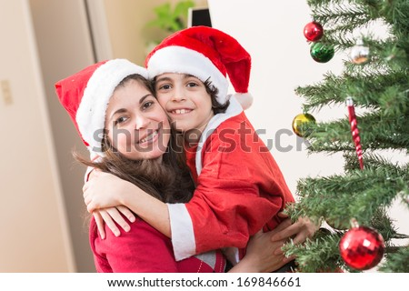 Hispanic family having fun and enjoying while putting together a Christmas tree at home. Latin single mother and son during Christmas - stock photo