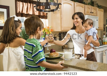 Hispanic family in kitchen with breakfast.