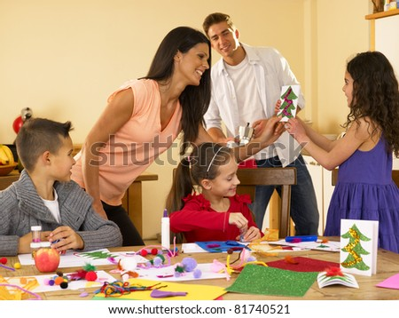 Hispanic family making Christmas cards - stock photo
