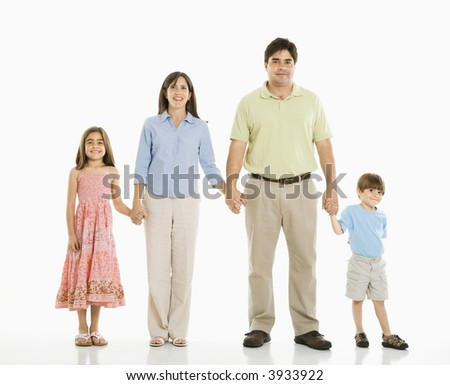 Hispanic family of four standing against white background holding hands. - stock photo