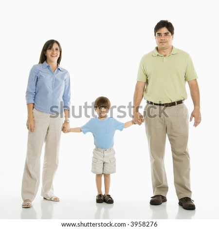 Hispanic family of three standing against white background holding hands.