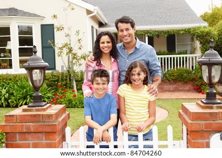 Hispanic family outside home - stock photo