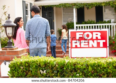 Hispanic family outside home for rent - stock photo
