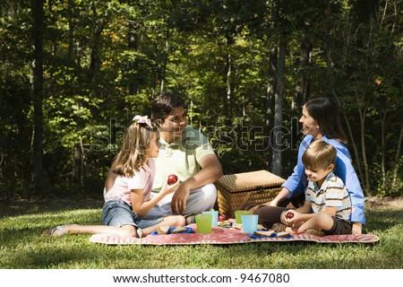 Hispanic family picnic in the park. - stock photo