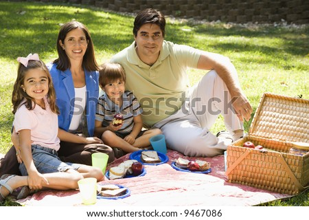 Hispanic family picnicing in the park and smiling at viewer. - stock photo