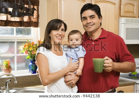 Hispanic family portrait in home kitchen with baby. - stock photo