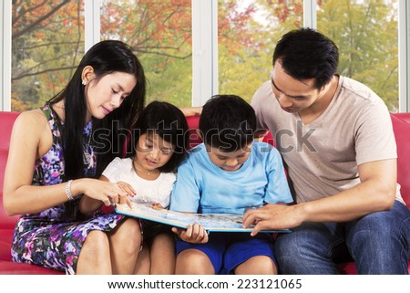 Hispanic family reading a story book together on couch with autumn tree background - stock photo