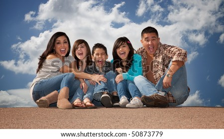Hispanic family seated against a cloudy sky