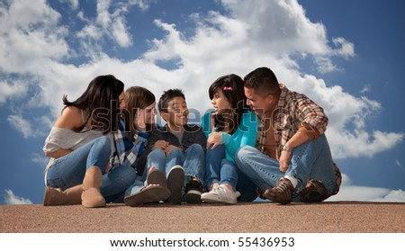 Hispanic family seated against a cloudy sky - stock photo