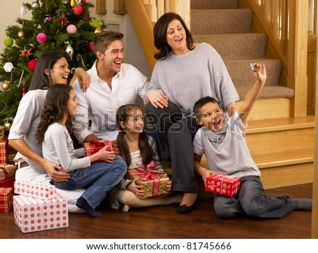Hispanic family taking photos at Christmas - stock photo