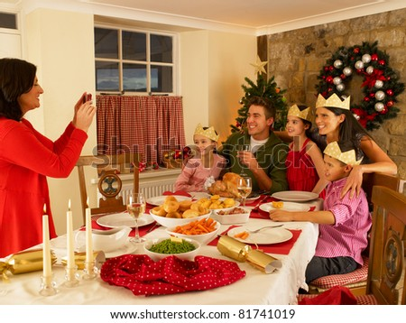 Hispanic family taking photos of Christmas dinner - stock photo