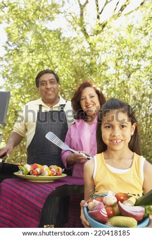 Hispanic family using barbecue grill - stock photo