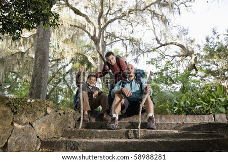Hispanic family with backpacks hiking in park resting - stock photo