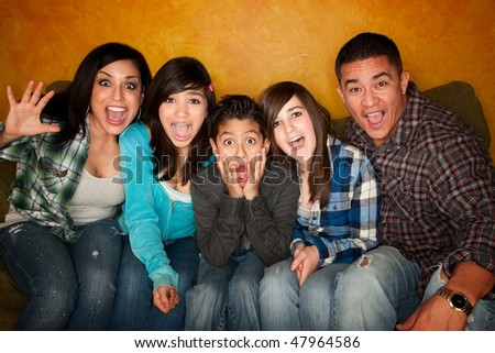 Hispanic Family with Big facial Reactions Sitting on Couch - stock photo