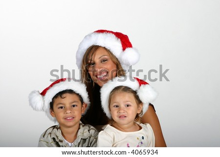 Hispanic family with mother, young son, and toddler girl wearing Santa hats