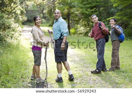Hispanic family with two boys hiking in woods on trail - stock photo