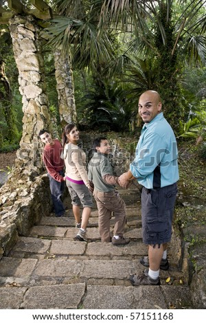 Hispanic family with two boys walking down stairs outdoors - stock photo