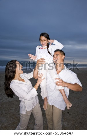 Hispanic family with 9 year old daughter having fun on beach - stock photo