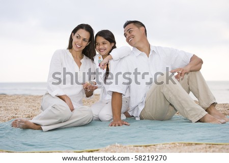 Hispanic family with 9 year old daughter on beach blanket - stock photo