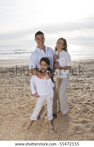 Hispanic family with 9 year old daughter standing on beach - stock photo