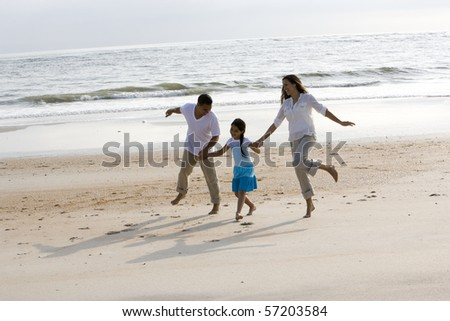 Hispanic family with 9 year old girl holding hands skipping on beach - stock photo