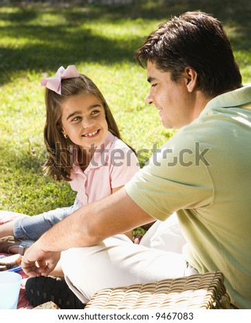 Hispanic father and daughter outdoors smiling at each and relaxing on grass. - stock photo