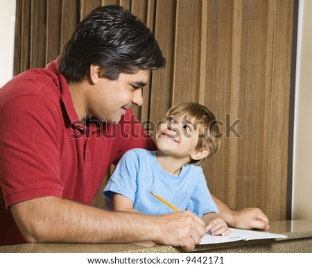 Hispanic father and   son doing homework and making eye contact. - stock photo